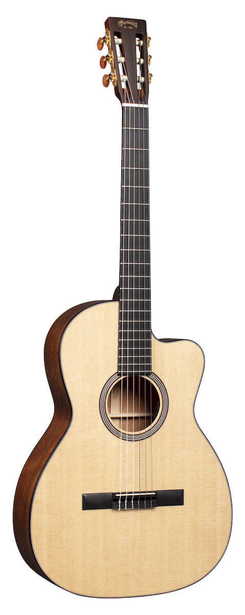 The Martin 000C12-16E crossover guitar standing against a white backdrop