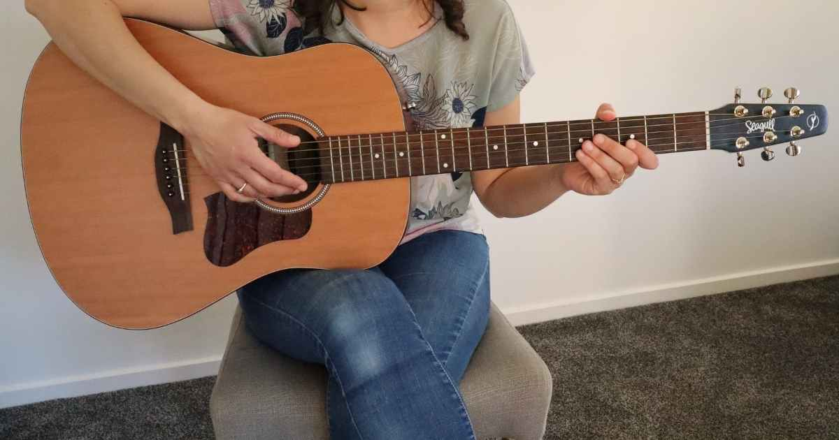 A woman with the Seagull 046386 S6 Original New 2018 Model Acoustic Guitar